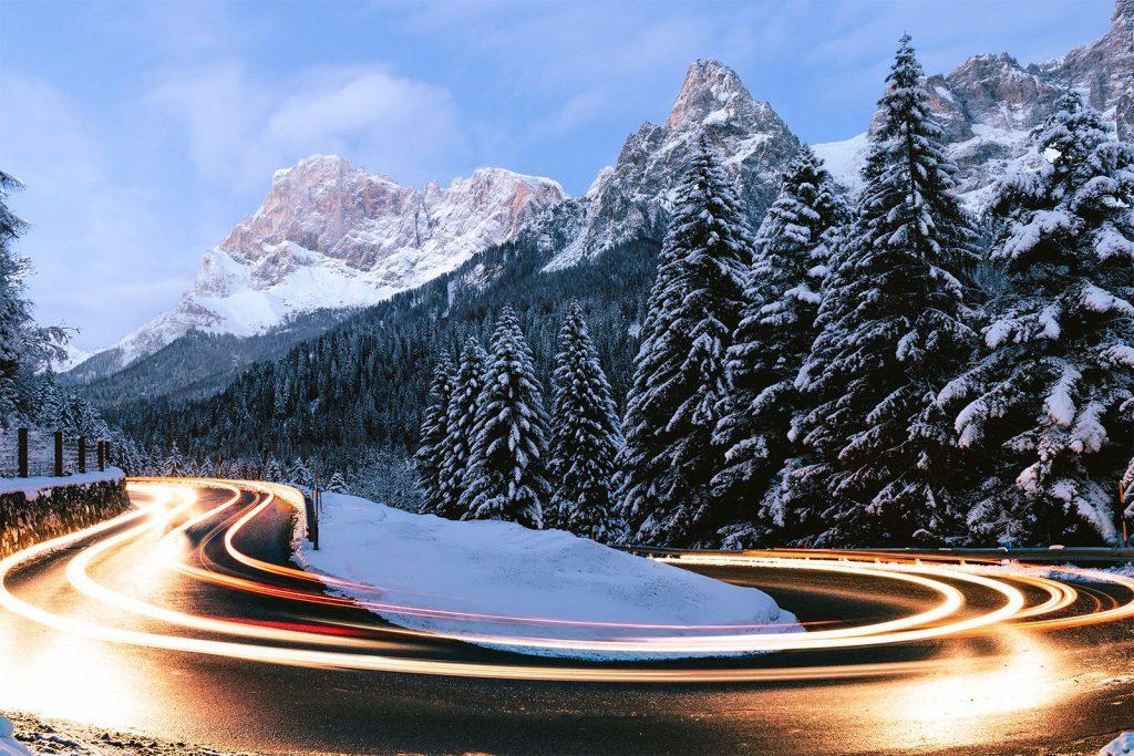 Tornante al tramonto con scie di auto - Capodanno Low Cost in Montagna