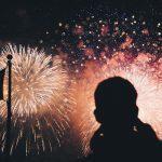 un ragazzo in ombra guarda i fuochi d'artificio a capodanno Low Cost